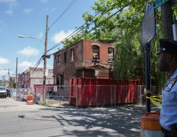 A police officer secures the block as investigators survey a demolition site that turned deadly at the corner of Jefferson and Bailey Streets in North Philadelphia on June 04, 2018.  (Lindsay Lazarski/WHYY)