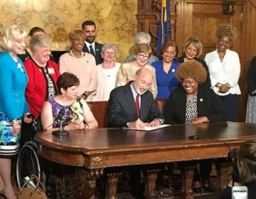 Gov. Tom Wolf signs an executive order, surrounded by supporters of the measure. (Katie Meyer/WITF)