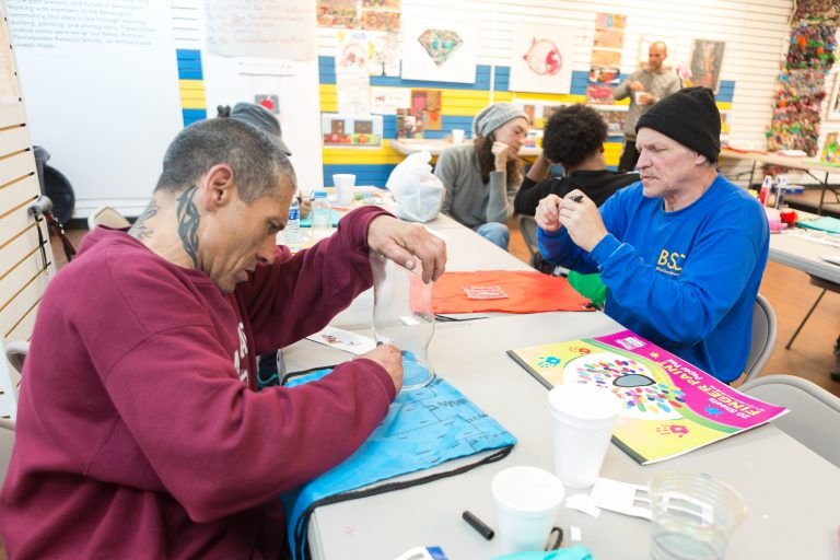 Kenan Nameli (left) and other workshop participants at the Kensington Storefront. Nameli lives in a nearby abandoned building, struggles with addiction, and said he has tried to enter into recovery a number of times. (Steve Weinik/Mural Arts)