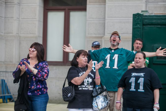 Mary Velez, (center), her daughter Elen, (right), and other Eagles fans sing the team's fight song at a rally for the team at City Hall Tuesday evening a day after President Trump canceled an event at the White House to honor the Super Bowl Champions. (Brad Larrison for WHYY)