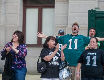 Mary Velez, center, her daughter Elen, right, and other Eagles fans sing the team's fight song at a rally for the team at City Hall Tuesday evening a day after President Trump canceled an event at the White House to honor the Super Bowl Champions. (Brad Larrison for WHYY)