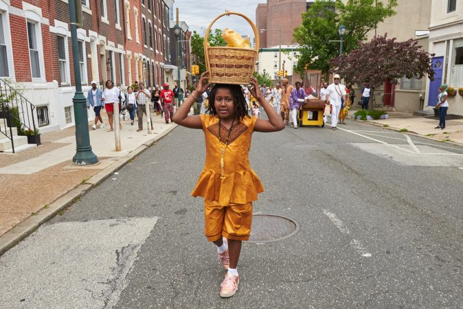 Anike Quinones, 9, balances an empty basket atop her head where offerings to Osun, the Yoruba goddess of the river, were once kept during Philadelphia's Odunde Festival on Sunday, June 10, 2018. (Natalie Piserchio for WHYY News)