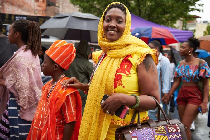 Ifadoyin Kemit of Trenton, N.J., stands with her son Ayanfe Kemit at the Odunde Festival in Philadelphia on Sunday, June 10, 2018. They travel back and forth to West Africa, where she finds her favorite fashion pieces. Her dress is from Nigeria and her purse is from Ghana. She made her scarf herself. (Natalie Piserchio for WHYY News)