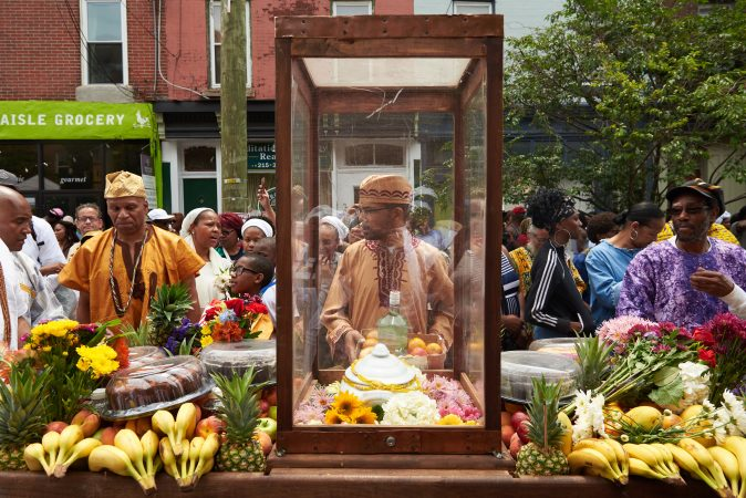The procession at the 2018 Odunde Festival in South Philadelphia is led with a cart of offerings including fresh fruit, flowers, cakes, and other biodegradable goods. (Natalie Piserchio for WHYY News)
