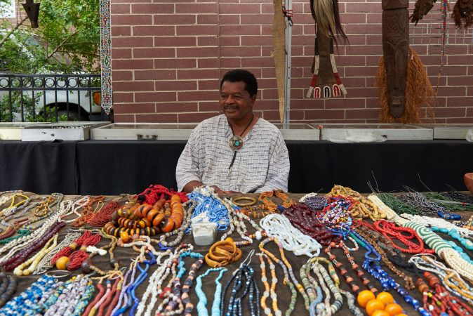 Otis Williams of Philadelphia sells African jewelry and figurines at the 2018 Odunde Festival in Philadelphia. He has been a vendor at the festival for roughly 30 years. (Natalie Piserchio for WHYY News)