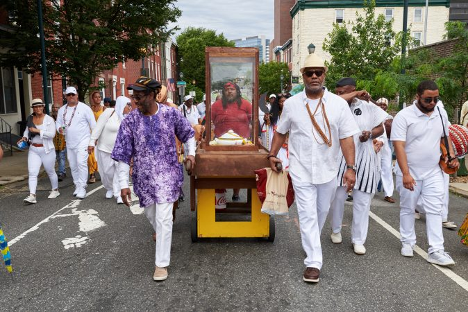 Akmal Muwwakkil (left) and Kerwin Capers (right) lead the empty procession stand back to the Odunde Festival in Philadelphia after offerings were given to the Schuylkill River on Sunday, June 10, 2018. The offerings included flowers, fruit, cake, and incense, amongst other biodegradable goods. (Natalie Piserchio for WHYY News)