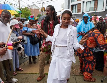 Fo'la'mi and Farugh dance a mix of West African on the corner of 23rd and Bainbridge streets as it begins to rain at the Odunde Festival on Sunday, June 10, 2018. Attendees of the festival play Djembe and other percussion instruments. (Natalie Piserchio for WHYY News)