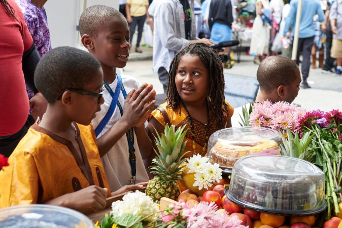 Sulayman Nabilla, 11, stands with Anike Quiones, 9, and prepares to cast offerings into the Schuylkill River as offerings to Osun, the Yoruba Goddess of the River during the Odunde Festival in Philadelphia on Sunday, June 10, 2018. (Natalie Piserchio for WHYY News)