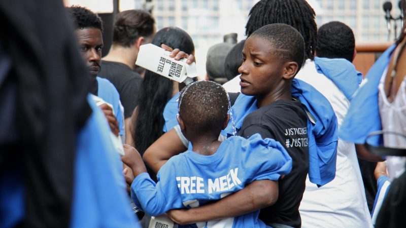 Shaatwion Moore, 21, pours water over her son,  Waalid Mickens, 2, to keep him cool during a rally in support of Meek Mill outside the courthouse where a hearing was taking place. (Emma Lee/WHYY)