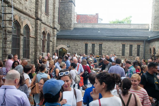 Guests gathered in the courtyard of the Church of The Advocate in North Philadelphia before Finding Sanctuary. (Brad Larrison for WHYY)