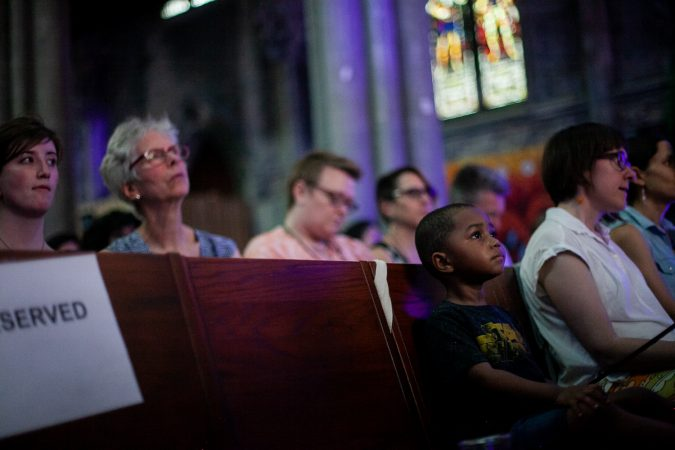 Guests listen to stories at the Finding Sanctuary storytelling event at Church of the Advocate in North Philadelphia. (Brad Larrison for WHYY)