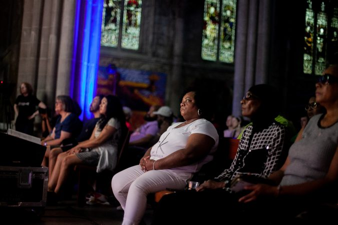 Guests listen to Jos Duncan, a multimedia producer, share her story at Finding Sanctuary at Church of the Advocate in North Philadelphia. (Brad Larrison for WHYY)