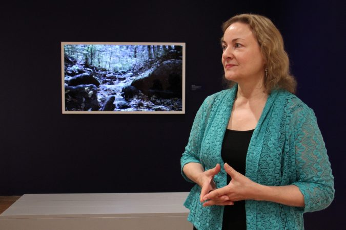 Curator Suzanne Ramljak stands before