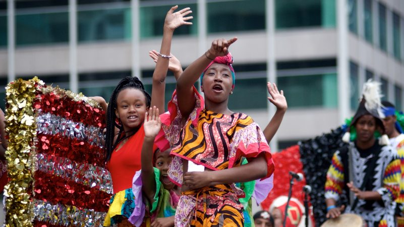 Juneteenth Parade participants wave from their float as they make their way through Center City, on Saturday. (Bastiaan Slabbers for WHYY)