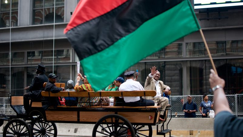 Congressman Dwight Evans representing Pennsylvania's 2nd District waves from the back of a horse-drawn carriage during the annual Juneteenth Parade on Market Street, on Saturday. (Bastiaan Slabbers for WHYY)