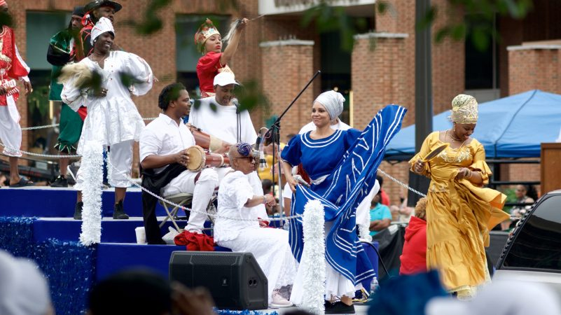 Peaches Jones (in blue dress), smiles atop the Kulu Mele float as it rolls past the viewing area at Independence Mall, during the annual Juneteenth Parade, on Saturday. (Bastiaan Slabbers for WHYY)
