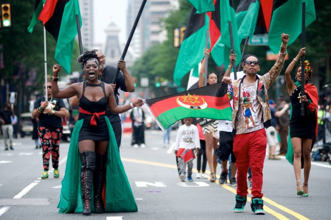 Leighdy Morris, Queen of the RBG brigade (left) raises a fist as she marches on Market Street during the annual Juneteenth Parade, on Saturday. (Bastiaan Slabbers for WHYY)