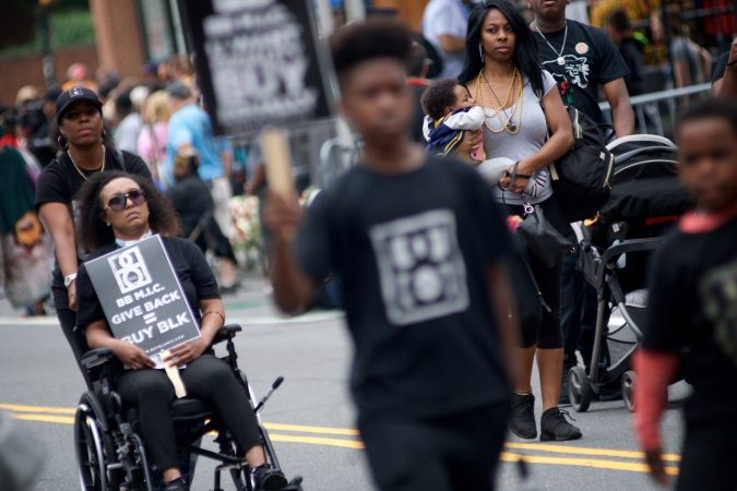 Parade participants promote the Buy Black campaign during the Juneteenth Parade, in Center City, on Saturday. (Bastiaan Slabbers for WHYY)