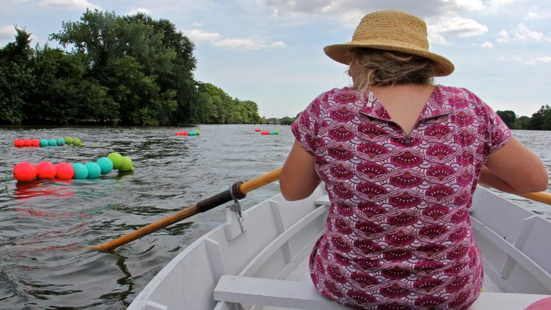 Stacy Levy uses a small rowboat to check on her tide buoy installation on the Schuylkill River. (Emma Lee/WHYY)