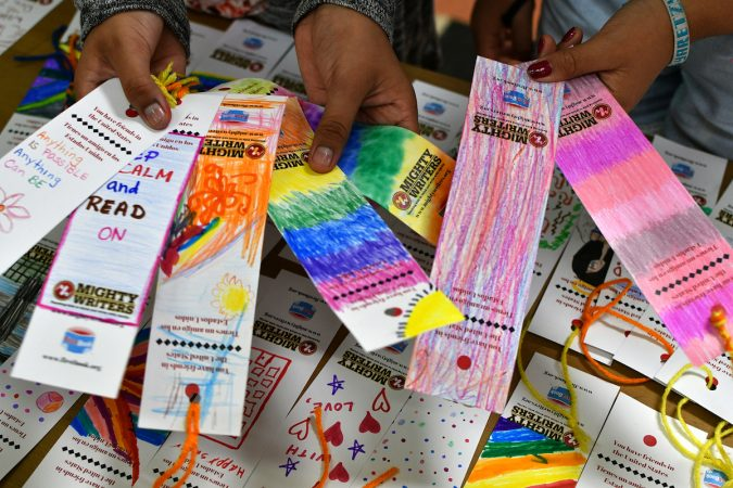 Alma, 11, and Yaretzy, 11, show some of the bookmarks they made at Mighty Writers El Futuro in South Philadelphia. (Bastiaan Slabbers for WHYY)