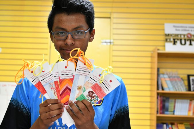 Robert, 14, holds up bookmarks representing the flags of Argentina, Spain, Panama, Colombia, and other countries, at Mighty Writers El Futuro in South Philadelphia. (Bastiaan Slabbers for WHYY)