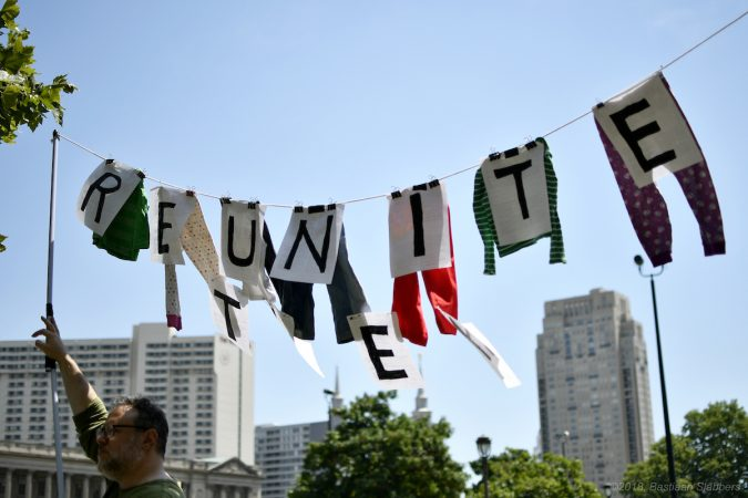 Dan Rothenberg of South Philadelphia holds up a sign made of hand-me-downs he once wore and which his daughter recently grew out of as he, joined by his family participates in a rally to protest Trump's immigration policies on Saturday in Philadelphia. (Bastiaan Slabbers for WHYY)