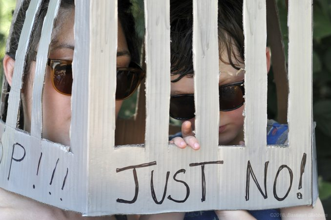 Jasper, 4, wears a jail-shaped box with his mother, Natalia Sadid of Wynwood, Pa., as they participate in the End Family Detention rally, at Logan Square, on Saturday. (Bastiaan Slabbers for WHYY)