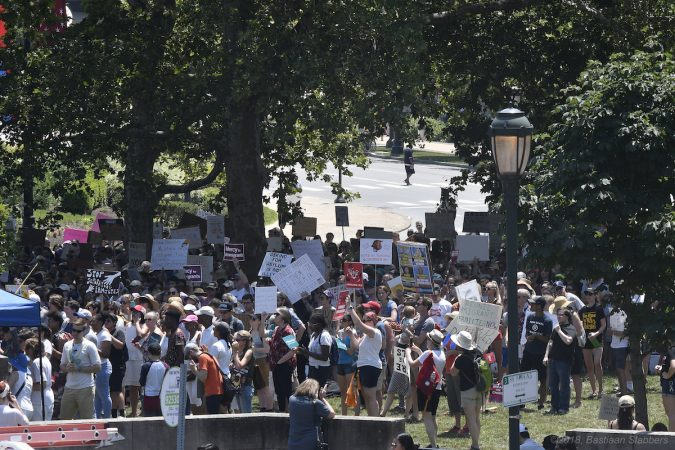 Protesters find shade under the trees as they listen to speakers during a rally against immigrant family detention, at Logan Square, on Saturday. (Bastiaan Slabbers for WHYY)
