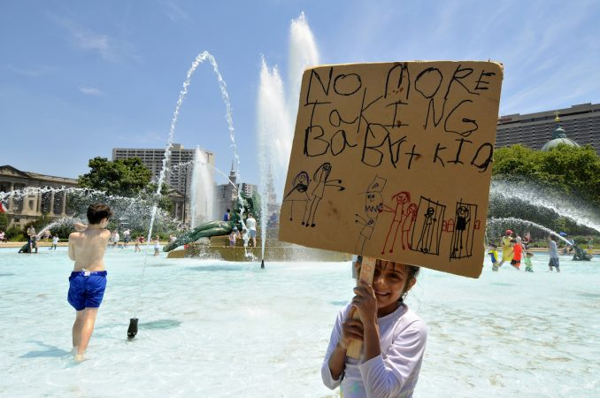 Olivia, 5, daughter of an undocumented immigrant father from Mexico, stands in the fountain holding a self-made sign as she participates in a rally against family detention Saturday in Philadelphia. (Bastiaan Slabbers for WHYY)