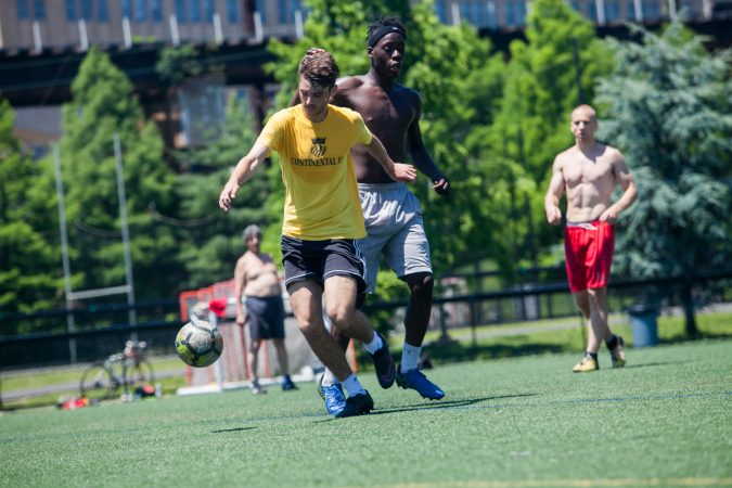 Players enjoy a game of pickup soccer at Penn Park on June 14, 2018. (Brad Larrison for WHYY)