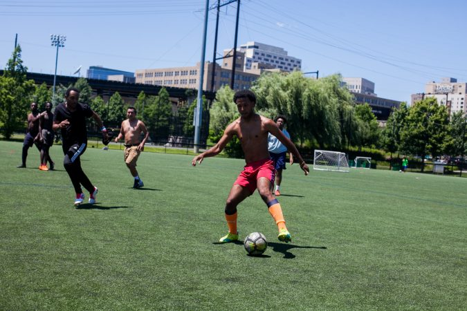 University of Pennsylvania students, workers, and community members play pickup soccer at Penn Park on June 14, 2018. Many were anticipating this year's World Cup tournament. (Brad Larrison for WHYY)