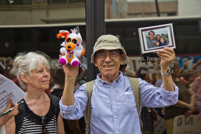 Ramon Garcia Castro holds up a photo of his family in Chile outside of the Center City offices of ICE to protest the practice of separating children from their families. (Kimberly Paynter/WHYY)