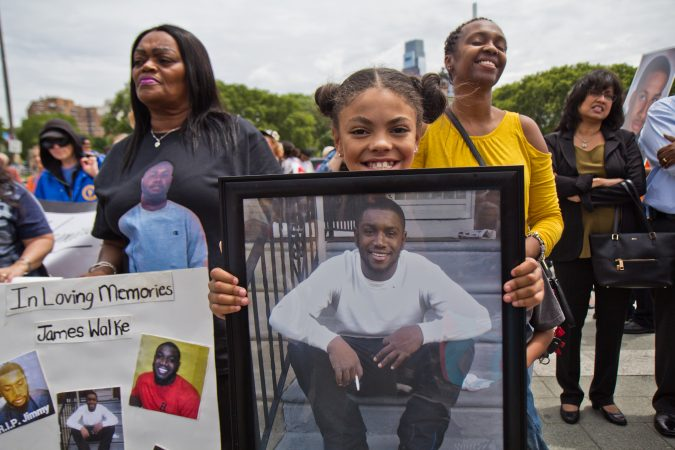 Kimora Ford, 10, holds a photograph of her stepfather, James Walke, to honor his memory at the demonstration against violence. (Kimberly Paynter/WHYY)
