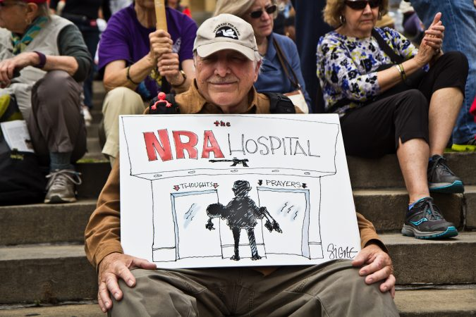 Ronald Instep holds up a Signe Wilkinson cartoon at the rally. (Kimberly Paynter/WHYY)