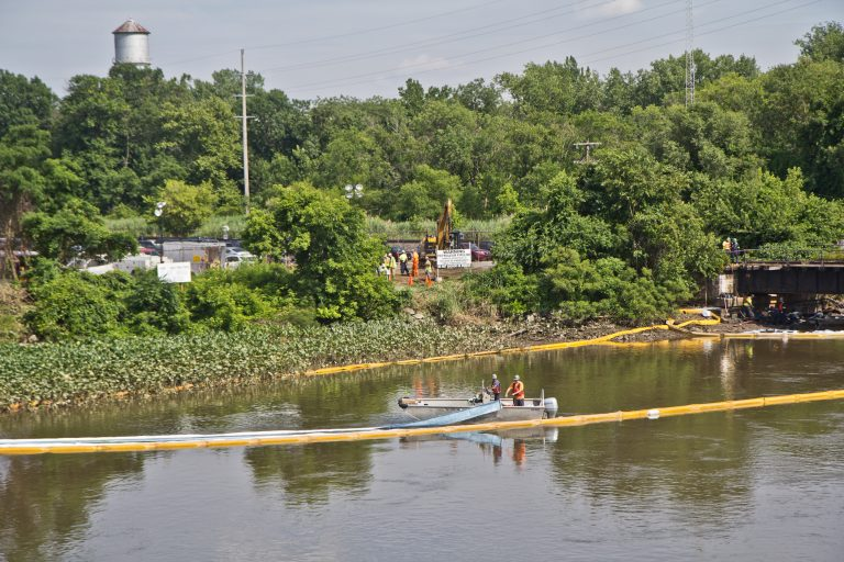 An environmental cleanup crew works to remove fuel from a spill in Darby Creek in Tinicum Township, Pennsylvania, near the Philadelphia International Airport. (Kimberly Paynter/WHYY)