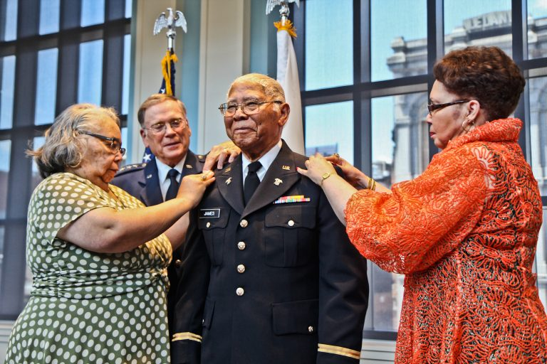 John Edward James Jr., an Army veteran of World War II, is pinned with the rank of second lieutenant by his daughters Brenda Roberta Watts (left) and Dr. Marion Teresa Lane. (Kimberly Paynter/WHYY)