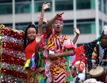 Juneteenth Parade participants wave from their float as they make their way through Center City