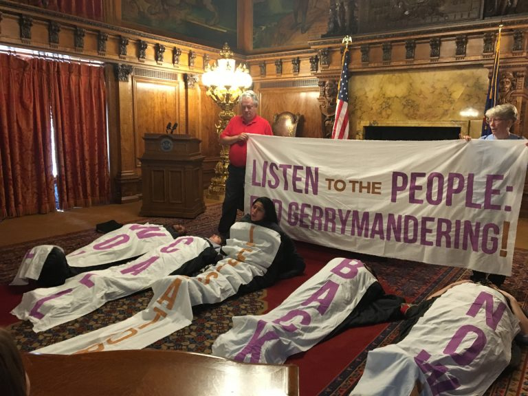 Amid chants and songs, sleeping bag-clad protesters sat up one by one to give speeches in favor of congressional and state district maps drawn by citizens, not politicians.