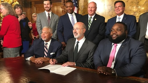 Philadelphia Senator Anthony Williams, Governor Tom Wolf, and Philadelphia Representative Jordan Harris pose for pictures after signing the Clean Slate bill. (Katie Meyer/WITF)