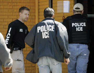 In this file photo, Immigration and Customs Enforcement agents enter a restaurant to remove evidence. (David Duprey/AP Photo)