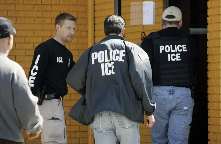 In this file photo, Immigration and Customs Enforcement agents enter a restaurant to remove evidence (David Duprey/AP Photo)