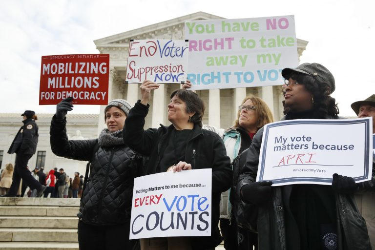 People rally outside of the Supreme Court in opposition to Ohio's voter roll purges, Wednesday, Jan. 10, 2018, in Washington.