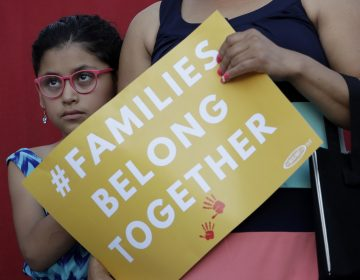 A girl stands with her mother during a Rally For Our Children event to protest a new