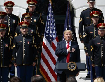 President Donald Trump sings the national anthem during a