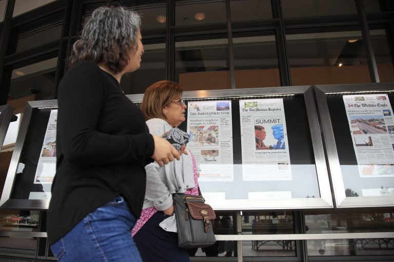 Newseum visitors browse newspaper front pages displayed outside the museum in Washington, Monday, June 11, 2018.