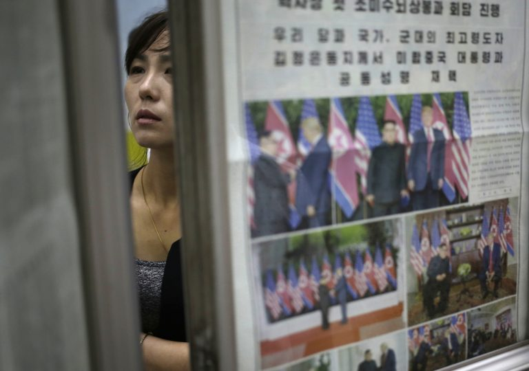 A woman reads newspapers fronting the news on President Donald Trump's summit with North Korean leader Kim Jong Un at Puhung subway station in Pyongyang, North Korea, Wednesday, June 13, 2018. The series of photos on the front page of the ruling workers' party newspaper showed something North Koreans never would have imagined just months ago — their leader Kim Jong Un warmly shaking hands with President Donald Trump. (Dita Alangkara/AP Photo)