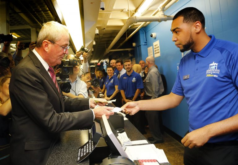 New Jersey Gov. Phil Murphy makes the first wager with Monmouth Park Sports Book ticket writer Quentin Harris, at Monmouth Park Racetrack Thursday in Oceanport, New Jersey. Major League Baseball has circulated a memo to teams, forbidding them and their broadcasting affiliates from accepting advertisements from sports betting outfits, such as Monmouth. (AP Photo/Noah K. Murray)