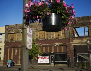 In this June 16, 2017, file photo, dilapidated storefronts stand along baskets of pink petunias that hang from light posts all over town, watered regularly by residents trying to make their city feel alive again in Aberdeen, Wash. From drivers paying more for gas and families bearing heavier child care costs to workers still awaiting decent pay raises to couples struggling to afford a home, people throughout the economy are straining to succeed despite the economy's gains. (AP Photo/David Goldman, File)