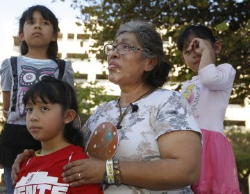 Lucia Ajas, middle, talks about her and her children, Regina Vargas, 7, left, Akemi Vargas, 8, second from left, and Trinidad Vargas, 5, right, being separated from their father during an immigration family separation protest in front of the Sandra Day O'Connor U.S. District Court building, Monday, June 18, 2018, in Phoenix.