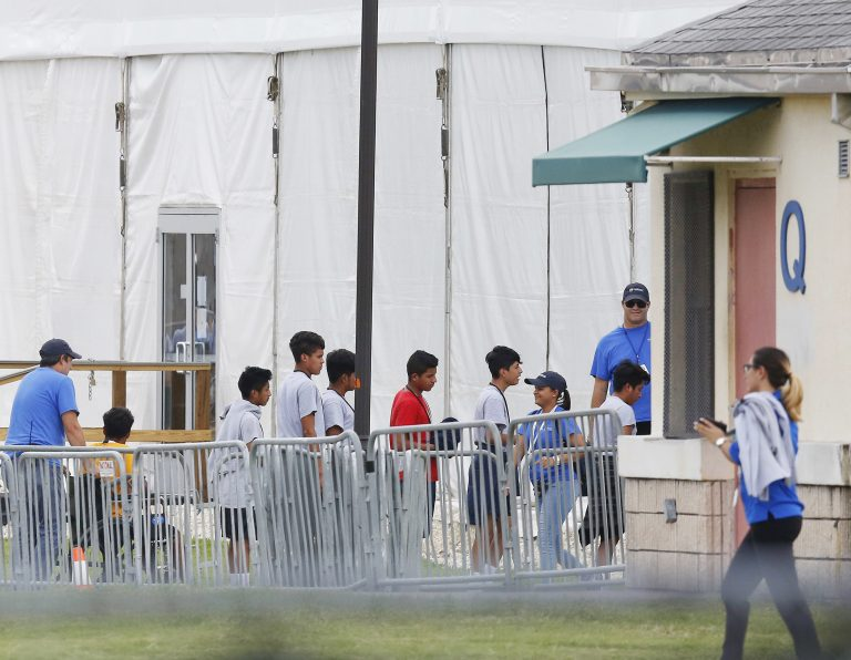 Immigrant children walk in a line outside the Homestead Temporary Shelter for Unaccompanied Children